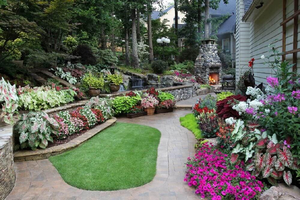 Cet aménagement paysager offre tout : une colline alpine, une pelouse, un étang artificiel, des parterres de fleurs et un coin salon avec barbecue et cheminée.