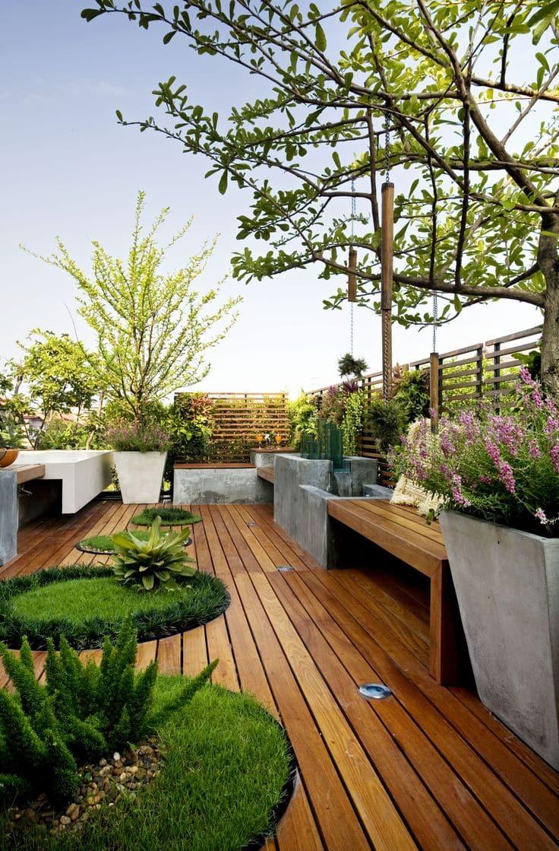 Aménagement paysager original utilisant du bois naturel, des parterres de fleurs et du béton