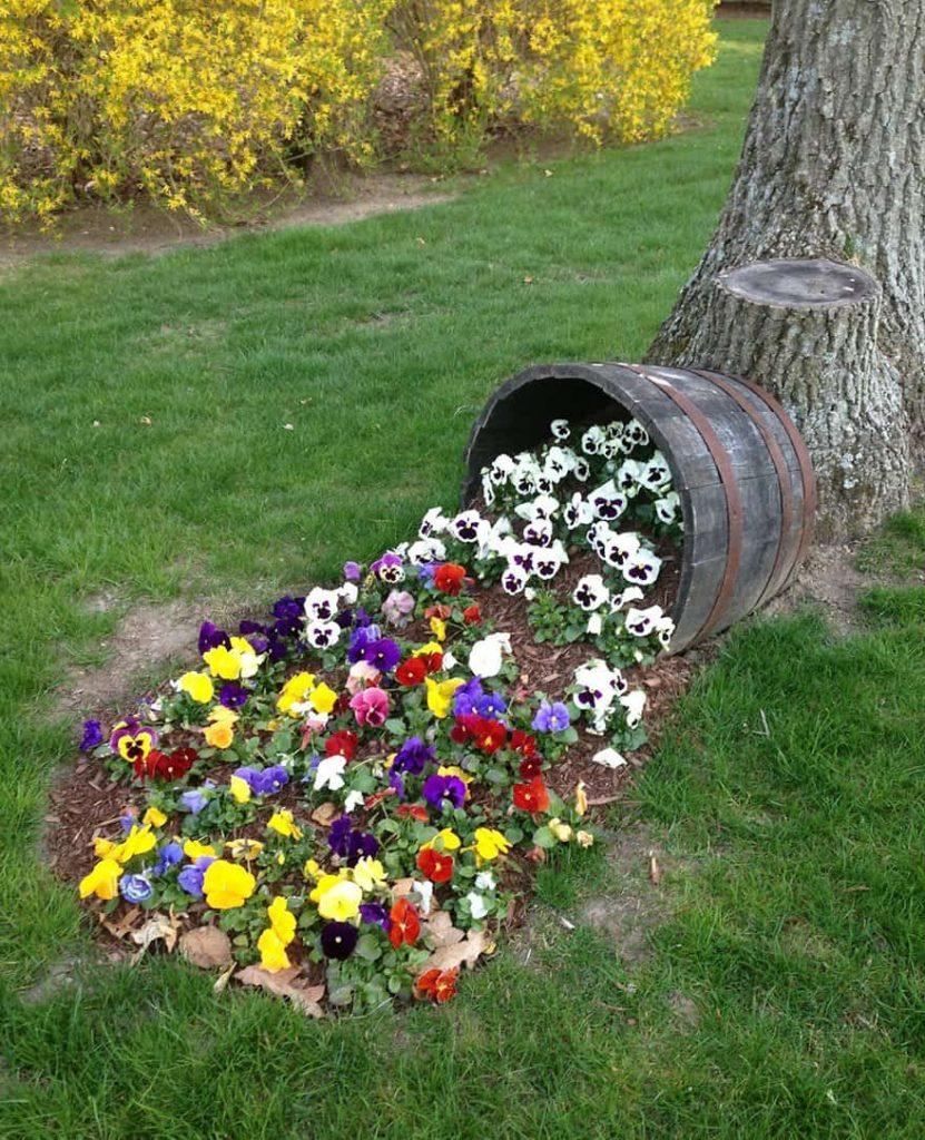 La solution originale d'un parterre de fleurs en forme de terre éparpillée d'un pot avec des fleurs de pétunias