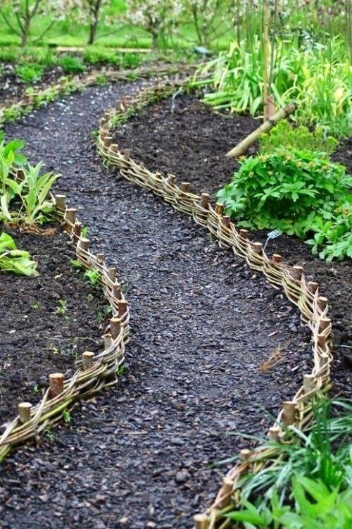 Невысокий плетеный забор для клумб будет хорошо смотреться в тандеме с низко растущими кустарниками