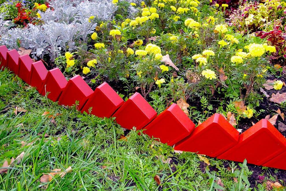 Очень необычно будет смотреться оградка из пластиковых элементов имитирующих красный кирпич