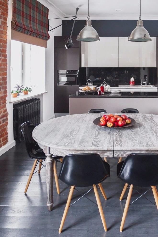 L'intérieur de la cuisine de style loft se marie parfaitement avec une table en bois à l'ancienne.