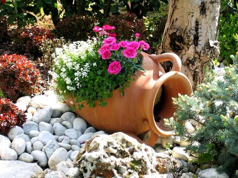 Un jardin de fleurs dans une cruche allongée est un excellent moyen de décorer le site
