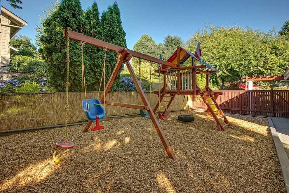 Il est souhaitable que le terrain de jeu ait un revêtement souple spécial.  L'écorce d'arbre déchiquetée est parfaite à ces fins.