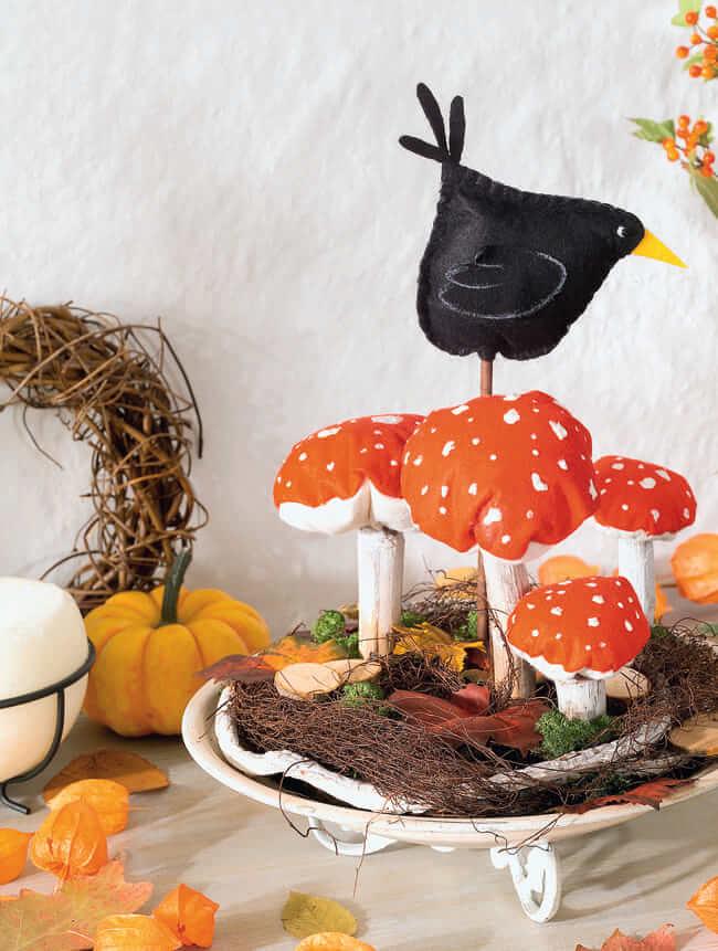 Une belle décoration pour la table faite de bâtons de bois collés aux coussins rembourrés en forme d'agaric de mouche