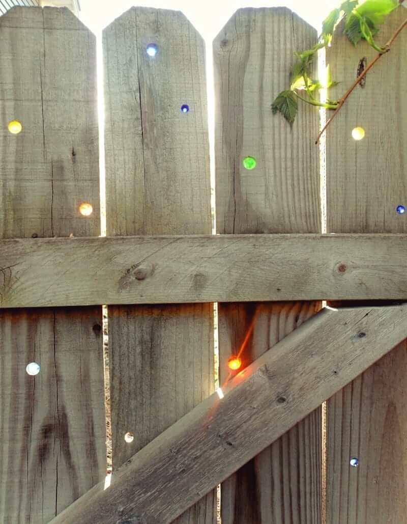 En perçant des trous de différentes tailles dans la clôture et en y insérant des pierres colorées, vous obtiendrez une belle clôture pour votre site
