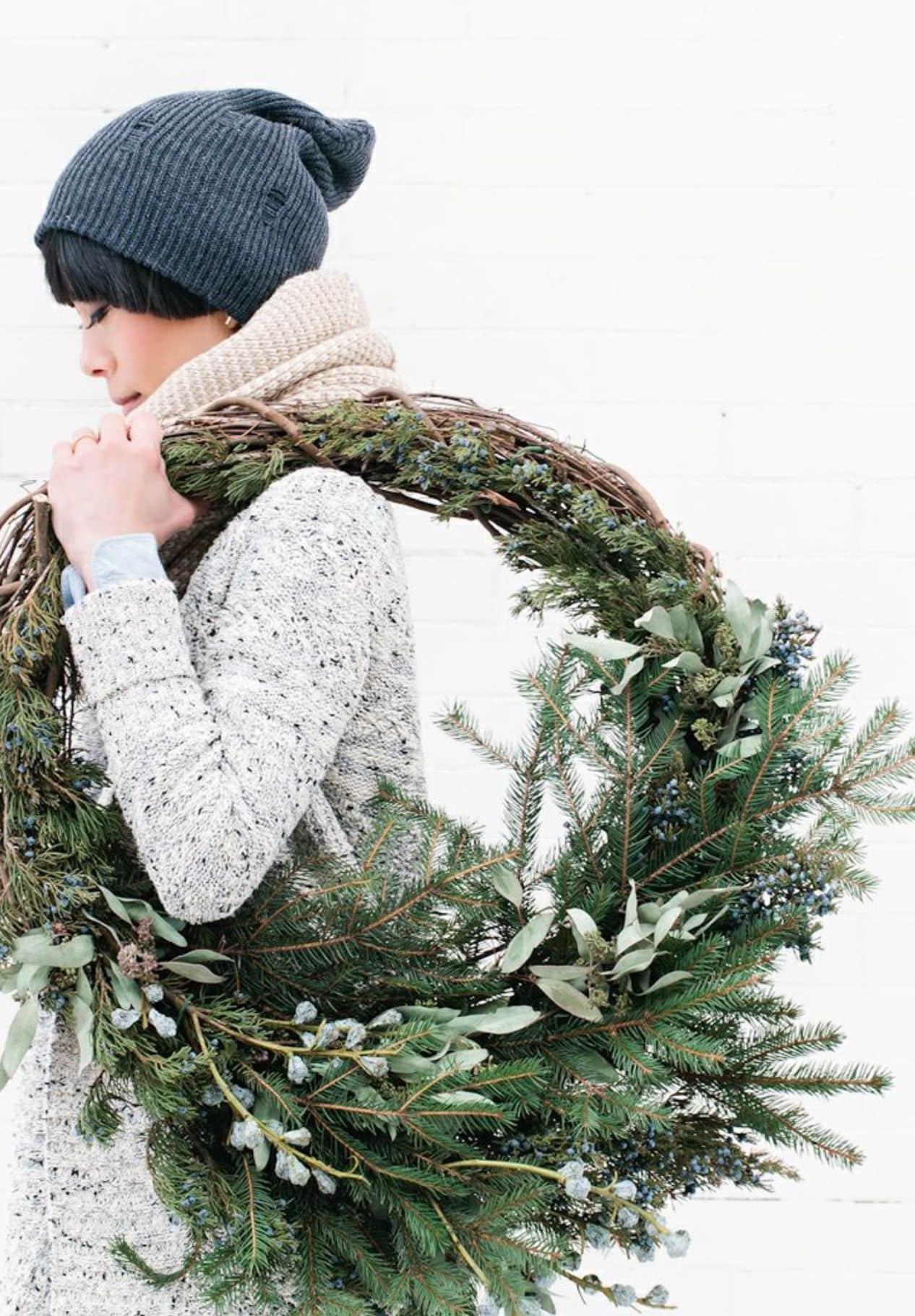 Добавить нотку свежести и природного тепла поможет новогодний венок из еловых лапок, связанных между собой в пучки