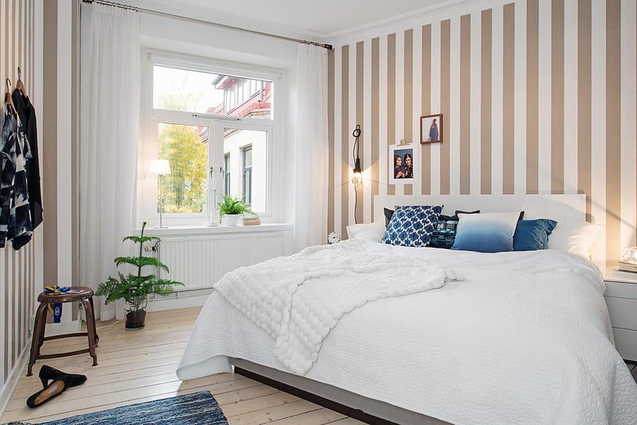 Le papier peint à rayures verticales contribuera non seulement à augmenter visuellement la superficie de la chambre à coucher, mais aussi à créer un intérieur vraiment magnifique.