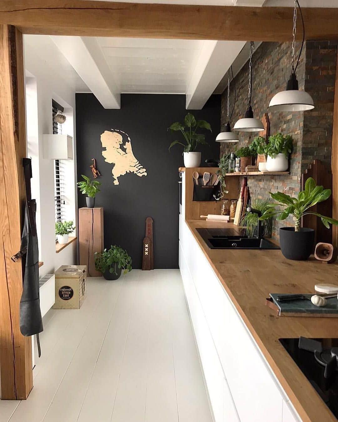 Une garniture blanche brillante avec un plan de travail en bois fait bonne figure avec un tablier de cuisine en briques décoratives.