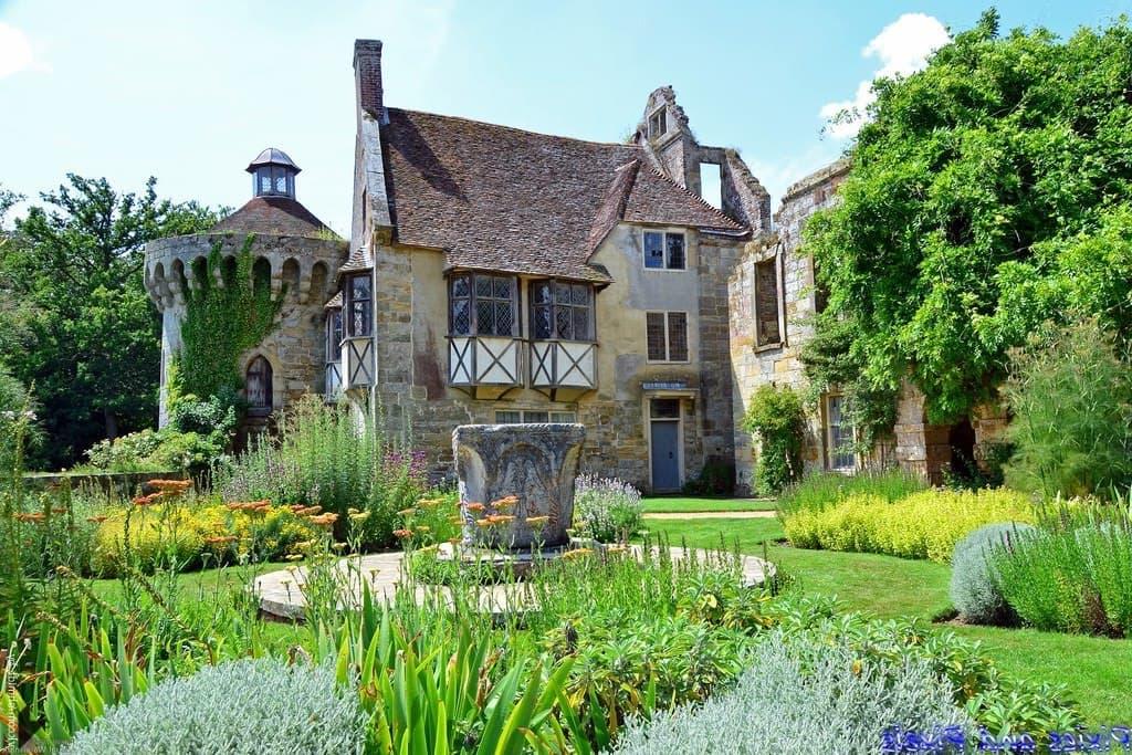 Un jardin d'une beauté fabuleuse avec une sculpture massive en béton au centre.