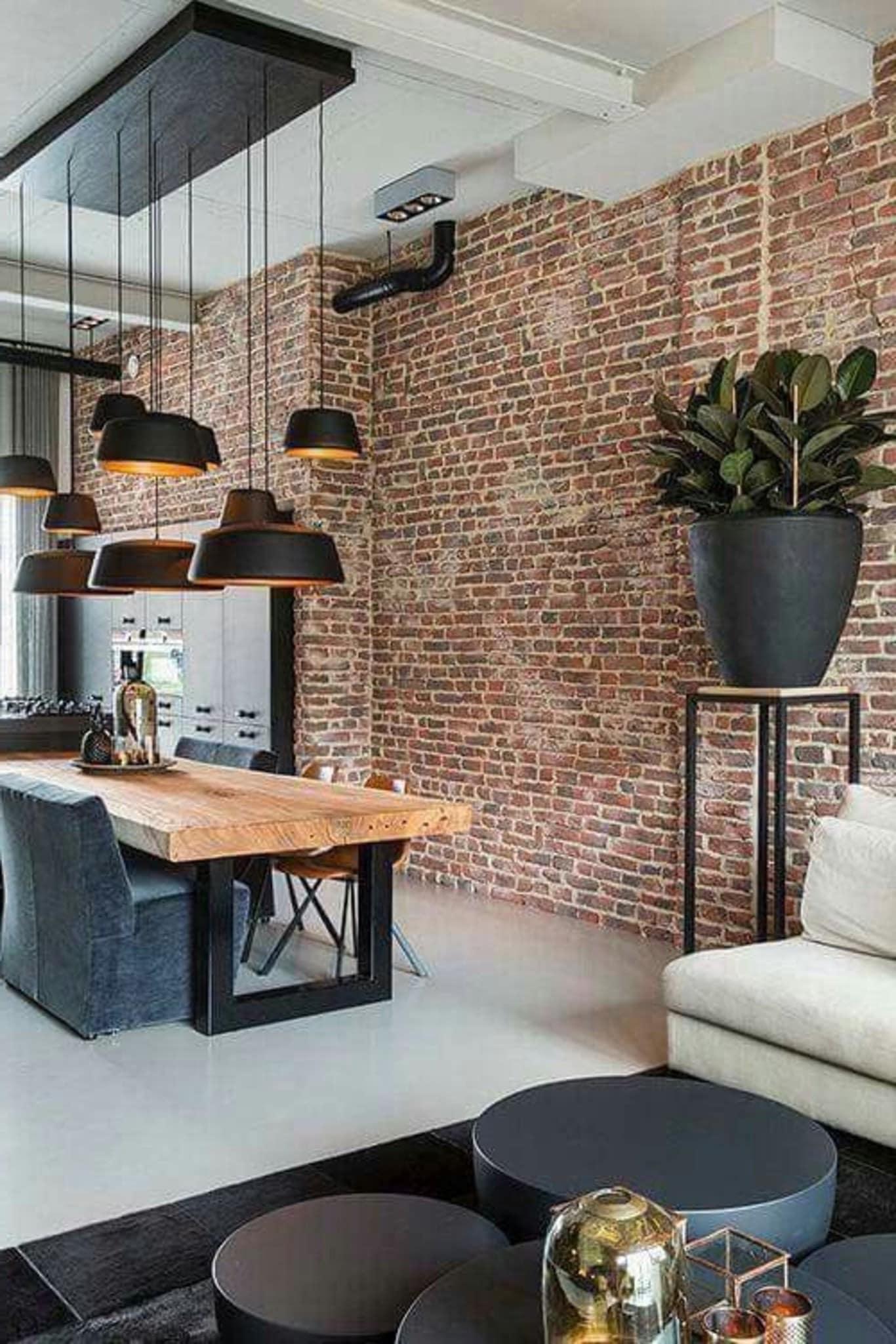 Aménagement de style loft avec une cloison spectaculaire en briques anciennes