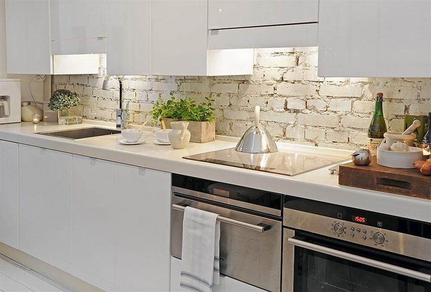 Отреставрированная кирпичная стена в интерьере белой кухни