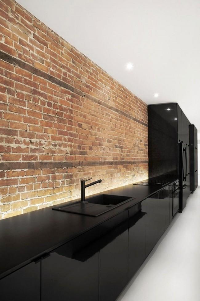 Черная глянцевая кухня и фартук из декоративного кирпича смотрится дорого и стильно