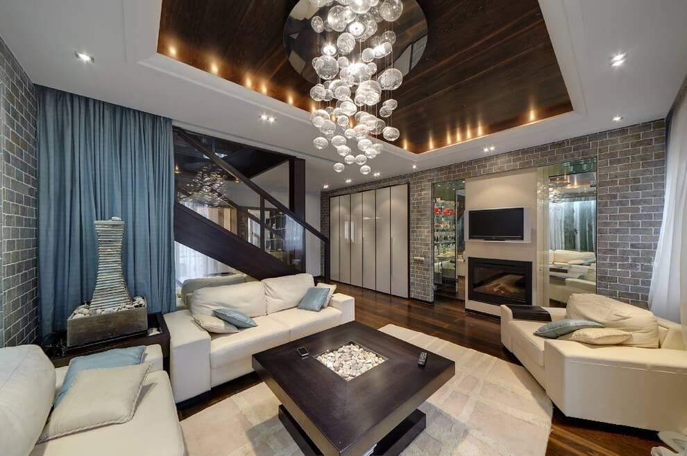 Стильная люстра свисающая с потолка является главным украшением данного интерьера гостиной