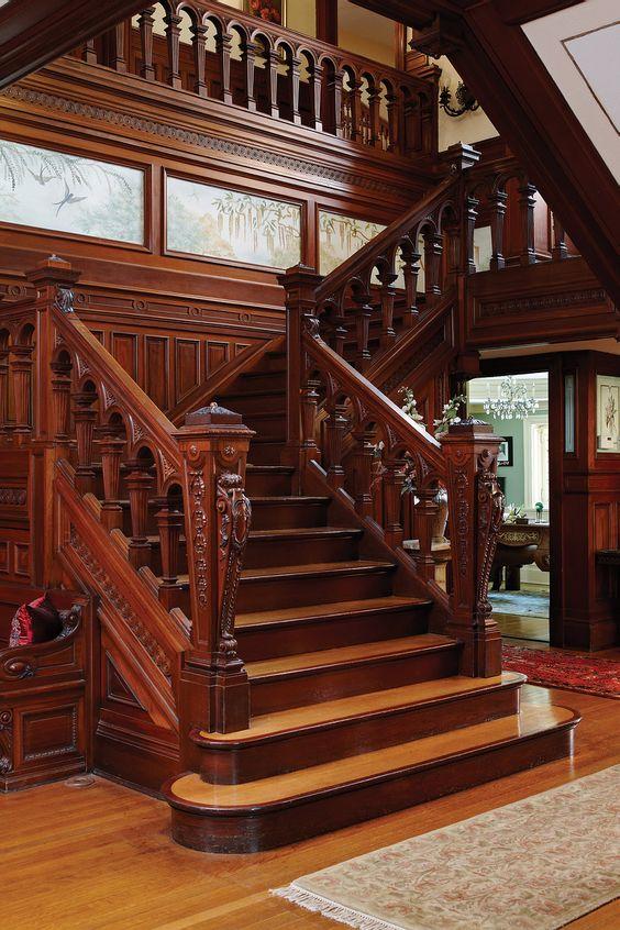Интерьер гостиной в классическом стиле с красивой деревянной лестницей на второй этаж