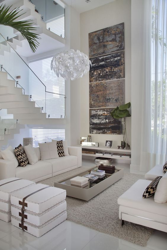 Воздушная белоснежная лестница с стеклянными перилами в гостиной