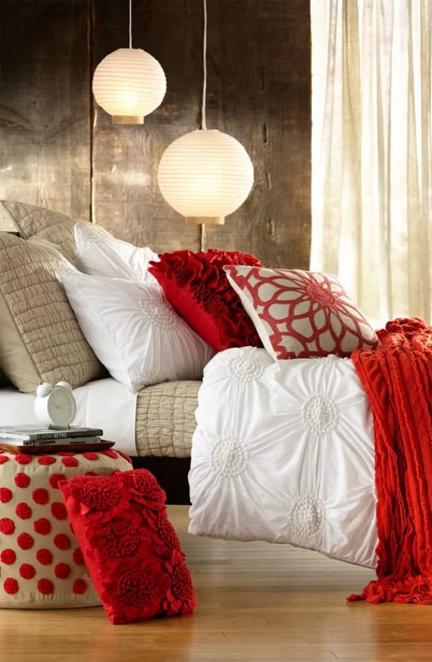 Сочетание белого с красным всегда дает положительный результат, а на фоне деревянных стен, интерьер спальни будет выглядеть более гармонично