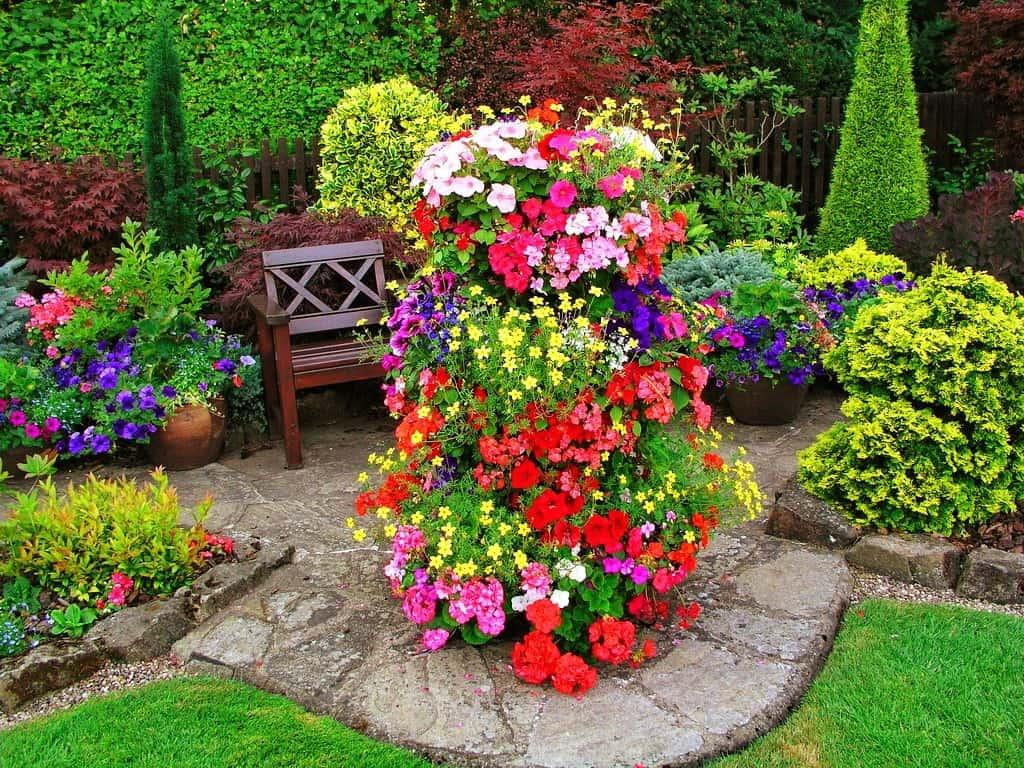 Яркую вертикальную клумбу из цветов лучше установить неподалеку от места для отдыха, так вы сможете постоянно любоваться своим детищем