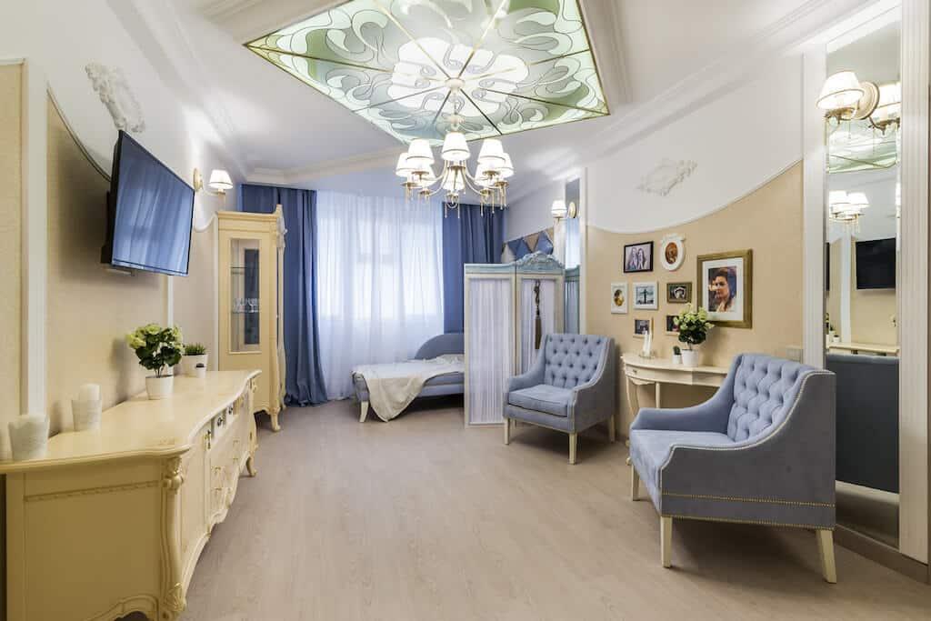 Завораживающий интерьер гостиной в классическом стиле с применением витражного стекла и лепнины на потолке