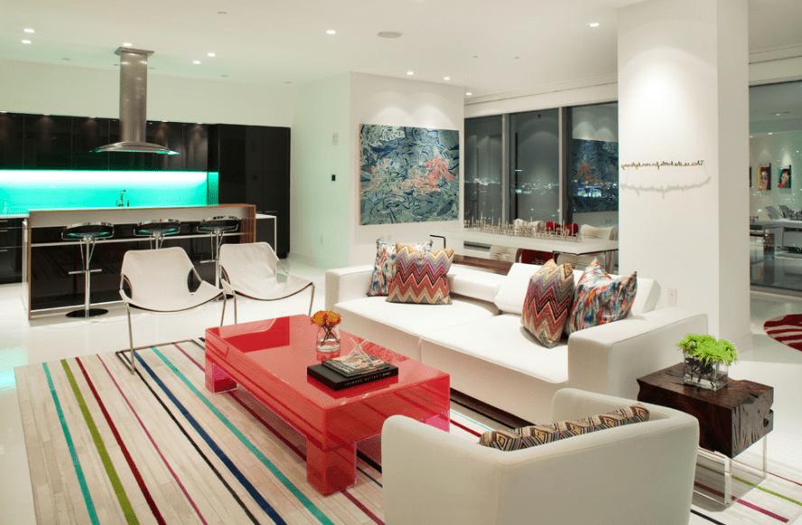 Разбавить белоснежное пространство поможет яркий журнальный столик и цветные подушки