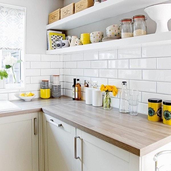 Желтый цвет будет хорошо смотреться в тандеме с глянцевым фартуком выполненный из белой керамической плитки