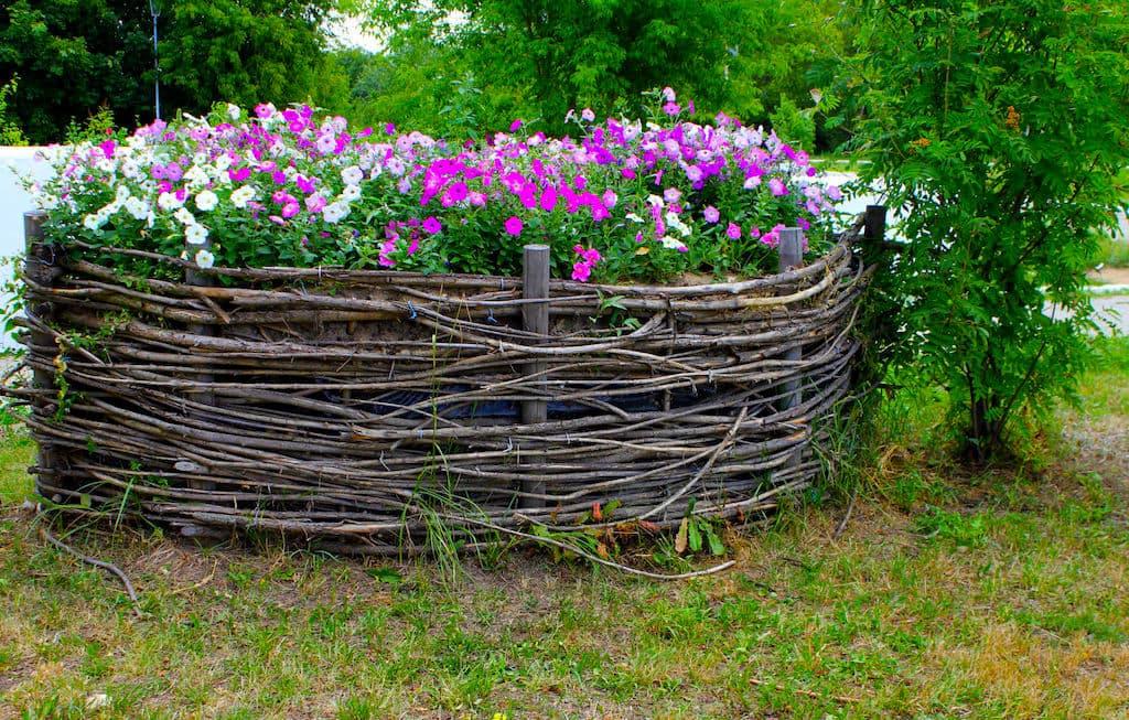Чтобы оформить свою клумбу в индивидуальном стиле, возведите для нее декоративное плетеное ограждение из веток ивы и лозы