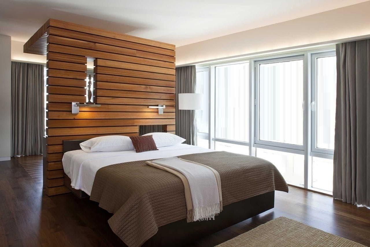 Стильное конструкция из дерева выполняющее двойную функцию: зонирование помещения и изголовье кровати