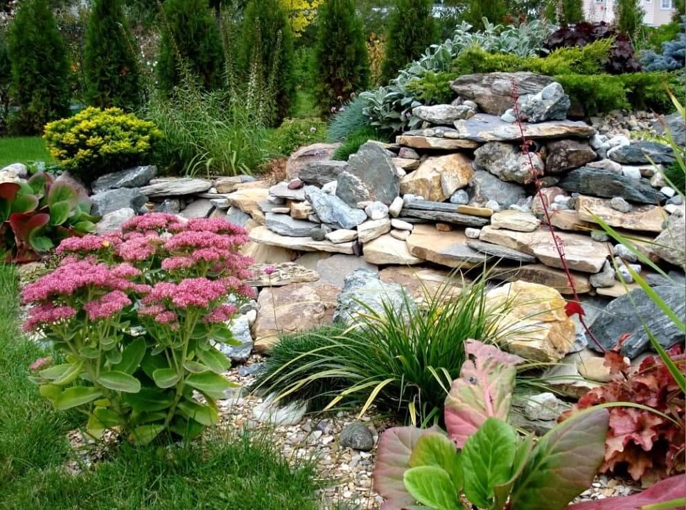 Прекрасная композиция из камней и красивых растений, имеющих различное время цветения