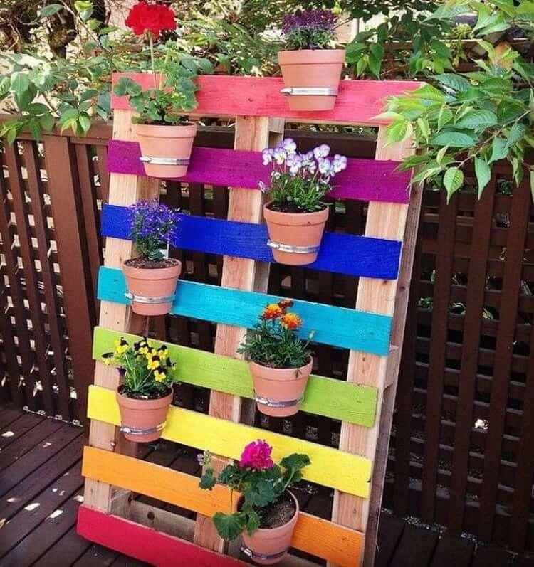 Использовав такие нехитрые материалы, как деревянный поддон, металлические хомуты и глиняные горшки с цветами, можно создать настоящее произведение искусства
