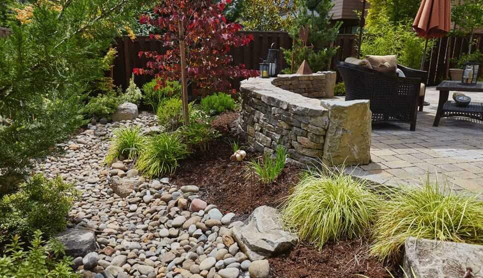 Сухой ручей на заднем дворе, выложенный из обычных полевых камней