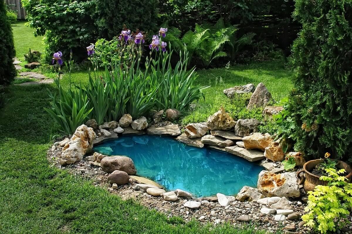Небольшой искусственный пруд на даче с чистой голубой водой