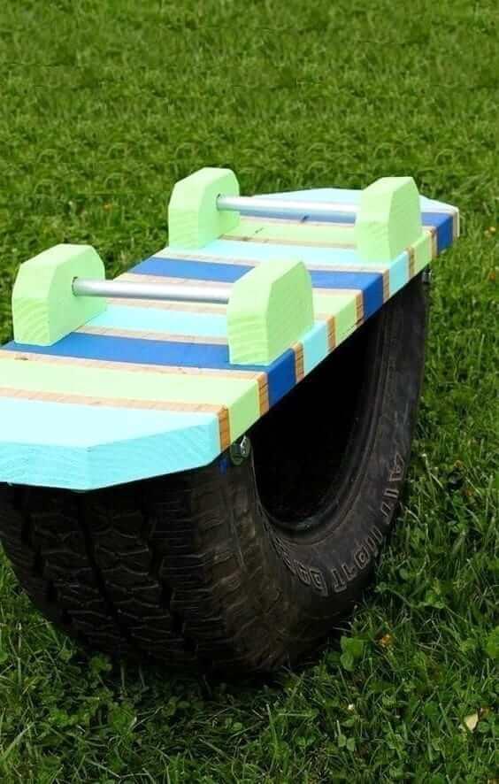 Разрезав колесо пополам и прикрутив к одной из частей доску с держателями, можно получить отличные качели-балансир