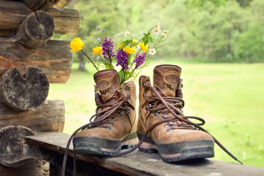 Если вам понравилась затея изготовления кашпо из обуви, но вы не хотите её портить, подойдет вариант использования ботинки в качестве обычной вазы, вставив в них свежесорванные цветы