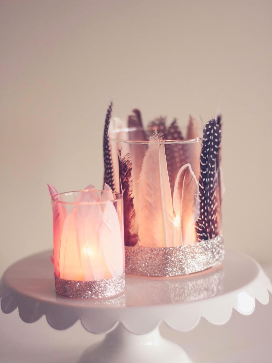 Создать невероятно романтическую обстановку можно с помощью декоративных подсвечников, выполненных из стеклянных стаканов и красивых перьев