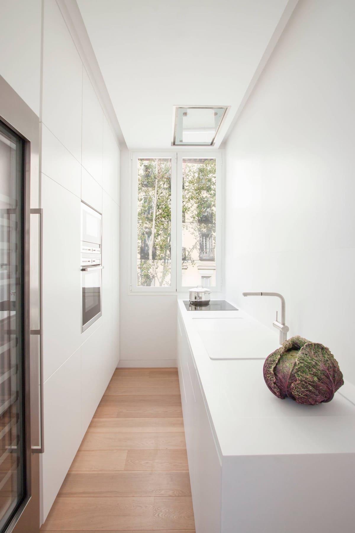 Белоснежная узкая кухня с хорошим естественным освещением
