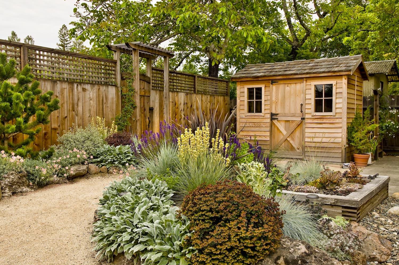 Двор в стиле кантри с большим количеством цветов и растений