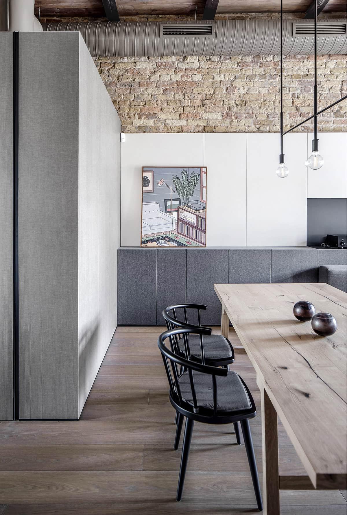 Обычный кухонный стол, сбитый из досок, в окружении красивых черных стульев прекрасно предает индустриальную стилистику оформления помещения