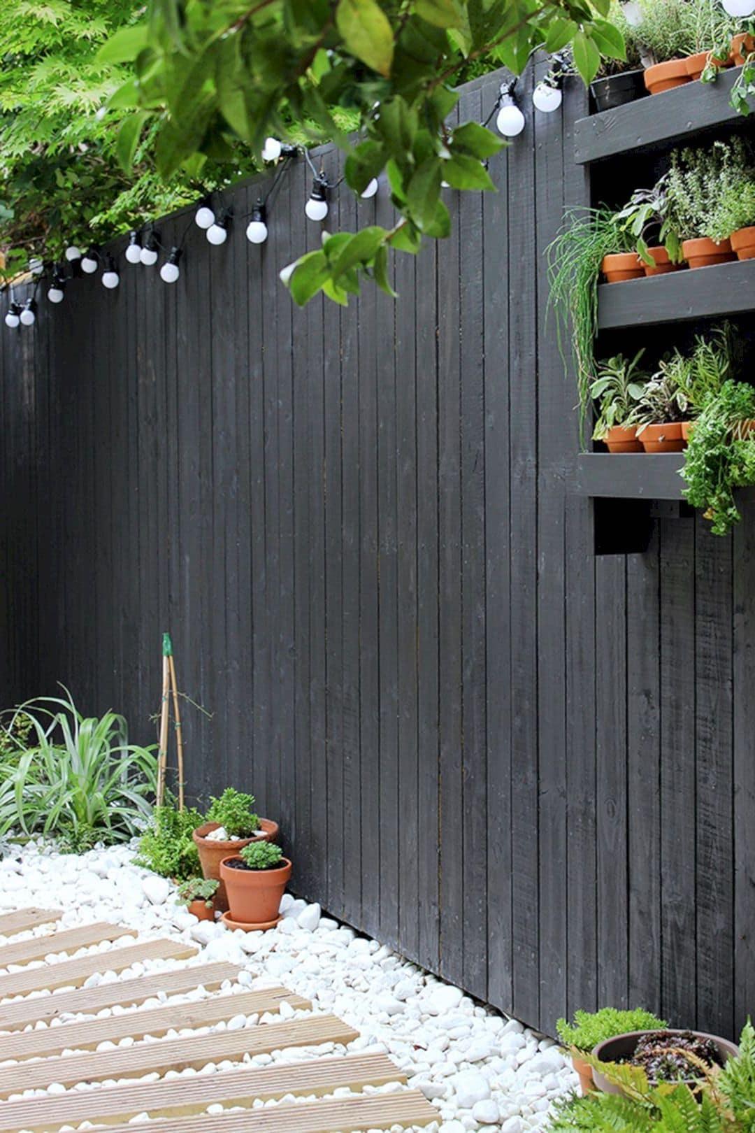 Забор из дерева, окрашенный в темный или даже черный цвет, подчеркнут белые камешки и яркая подсветка