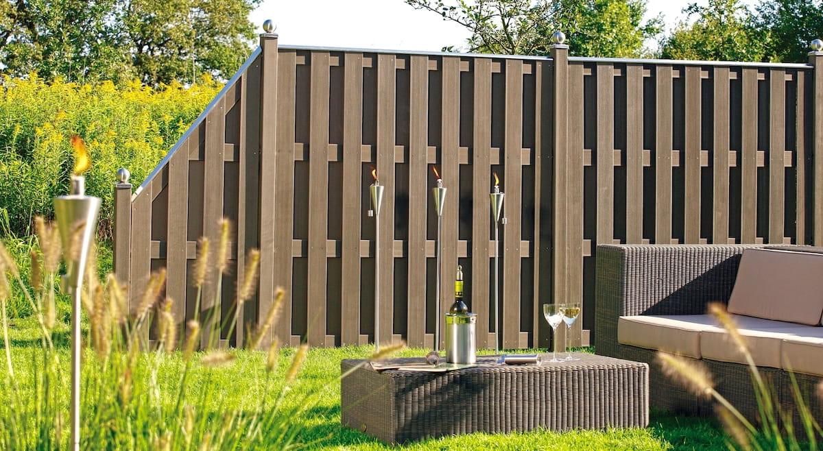 Невысокая ограда из деревянного штакетника гармонирует с мебелью из ротанга